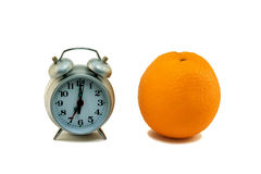 Gray alarm clock and orange isolated on a white Stock Photography