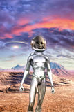 Gray alien and UFO in the desert. 3D render illustration Royalty Free Stock Photo