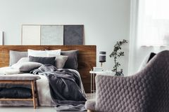 Gray armchair facing white bed. Close-up of comfy, gray armchair facing white bed with gray bedsheets and wooden bedhead in cozy bedroom interior Stock Photography