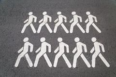 On the gray asphalt icons with the image of walking men white. royalty free stock photo