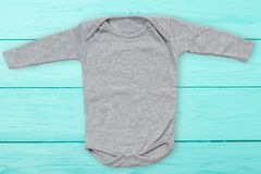 Gray baby mock up jumpsuit on blue wooden background. Baby bodysuit mockup and template blank copy space. Top Front view.