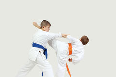 On a gray background two sportsmen are doing paired exercises karate Stock Photography
