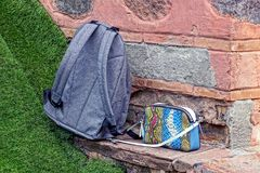 A bag and a backpack stand on the lawn near the wall in the street Royalty Free Stock Images