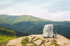 Gray backpack with a plastic bottle of drinking water on top of a mountain stock image