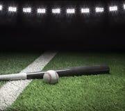 Gray baseball bat and ball on field with stadium lights Royalty Free Stock Photo