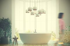 Gray bathroom interior, tub, girl. White and green tiles bathroom interior with a large window, a white round tub, a tree in a pot and a white lamp. A woman. 3d Stock Photography