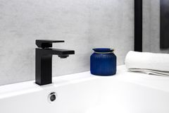 Gray bathroom interior with white sink black modern techno style faucet blue glass jar and white towel.  Royalty Free Stock Photography