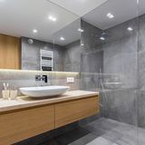 Gray bathroom with long countertop. Mirror and walk in shower royalty free stock image