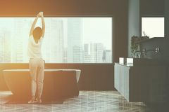 Gray bathroom with tub and sink, woman. Woman in bathroom with gray walls, wooden floor, white tub standing under big window and double sink on white countertop royalty free stock photo
