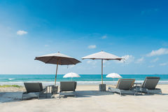 Gray beach chairs and parasols on sandy beach with cloudy blue s Stock Photo