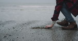 Gray beach closeup capturing video of a man have a meditation time beside of a seashore on a rain day. stock footage