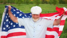 A gray-bearded man with the flag of the United States celebrates Independence Day on July 4.  stock video footage