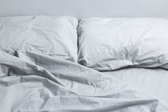 Gray bed linen. Messy bed with two pillows, gray bed linen Stock Photos