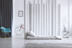 Gray bed and tube divider. Gray carpet and bed next to a tube divider in modern bedroom interior for a bachelor Royalty Free Stock Photos