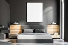 Gray bedroom interior, frame poster close up. Gray bedroom interior with a concrete floor, a king size bed and a frame vertical poster hanging above it. A close Stock Image