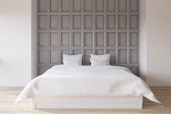 Gray bedroom interior. Interior of a bedroom with white and gray wooden wall element and a double bed with white bedding. 3d rendering Stock Photos