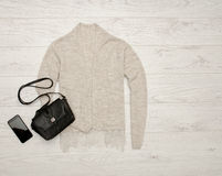 Gray-beige cardigan with lace, black handbag, phone. Fashion concept. Top view, space for text Royalty Free Stock Photography