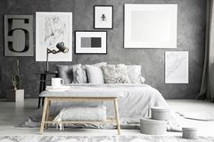 Gray bench in elegant bedroom. Gray bench standing in front of the bed in elegant bedroom interior with lamp on a bedside table stock image