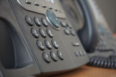 Gray and black business wired phone with receiver, dial and large display in the business office environment Stock Photo
