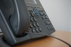 Gray and black business wired phone with receiver, dial and large display in the business office environment Stock Image