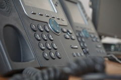 Gray and black business wired phone with receiver, dial and large display in the business office environment. Dark gray and black business wired phone with Royalty Free Stock Photos
