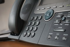 Gray and black business wired phone with receiver, dial and large display in the business office environment Royalty Free Stock Photography
