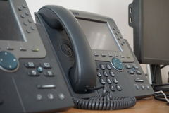 Gray and black business wired phone with receiver, dial and large display in the business office environment Stock Photography