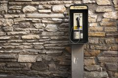 Gray and Black Telephone Booth Standing Near Gray Stone Wall at Daytime Royalty Free Stock Photo