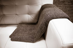 Gray blanket draped over a leather couch Royalty Free Stock Photography