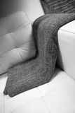 Gray blanket draped over a leather couch Stock Photography