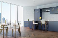 Gray and blue kitchen with a table. Gray tiled kitchen with panoramic windows, a wooden floor, a dining table with white chairs and dark blue countertops and Stock Photo