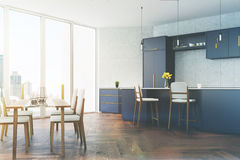 Gray and blue kitchen with a table toned. Gray tiled kitchen with panoramic windows, a wooden floor, a dining table with white chairs and dark blue countertops Stock Image