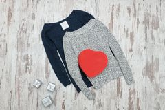 Gray and blue knitted sweater. Silver and red heart shaped gift. Boxes. Fashionable concept Royalty Free Stock Photo