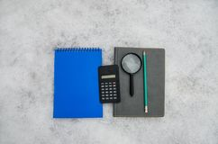 A gray and blue notepad, a pencil, a calculator and a magnifying glass on a white background stock photos