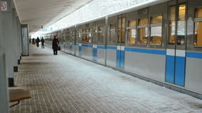 Gray-Blue Train Arrives at the Station and People Wait in Winter on Platform. Gray-Blue Train Arrives at the Station and People Wait in Winter. Train Stops near stock footage