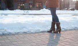 Gray boots with heels with white fur. And buckles on paving stones with snow Royalty Free Stock Photography
