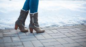 Gray boots with heels with white fur. And buckles on paving stones with snow Stock Image