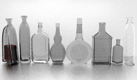 Gray bottles in a row. Several empty different glass bottles, different shapes, one bottle contains red liquid, 3D illustration over a gray background Stock Photo