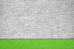Gray brick wall on grass field. Gray brick wall on green grass field Royalty Free Stock Photography