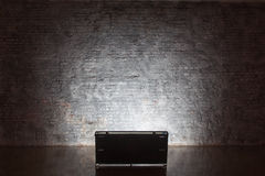 Brick wall lit by lamp Stock Images