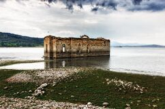 Gray and Brown Building on Body of Water Under Cloudy Sky during Daytime Royalty Free Stock Images