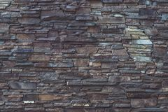 Gray and brown dilapidated stone texture of facade building. Rough brickwork, dirty weathered, grey dilapidated wall background. G royalty free stock photo