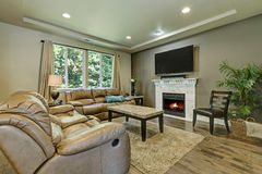 Gray and brown family room interior. Furnished with leather sofas, television on the fireplace shelf and cocktail table with marble top. Northwest, USA Royalty Free Stock Images