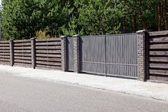 Gray brown gate and a fence in front of an asphalt road Royalty Free Stock Image