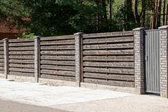 Gray brown gate and wooden fence in front of an asphalt road Stock Photo