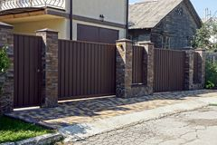 Gray brown iron fence in front of an asphalt road. Iron fence in the street in front of a private house Royalty Free Stock Photography