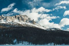 Gray and Brown Mountain Covered by White Snow Under Cloudy Sky during Daytime Stock Image