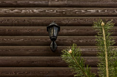 Gray brown old log wall and old lamp, background with wood texture Stock Photography