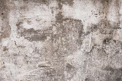 Gray and brown shabby concrete wall with flaky plaster. Torn rough old cement wall texture, background. Vintage, natural cracked d. Istressed background. Empty royalty free stock photo