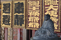 Gray Buddha Sculpture. Dates back to 1800s against a row of ancient Chinese plaques with inscriptions Royalty Free Stock Photos